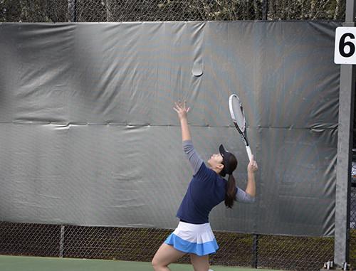 Women's tennis team serving ball