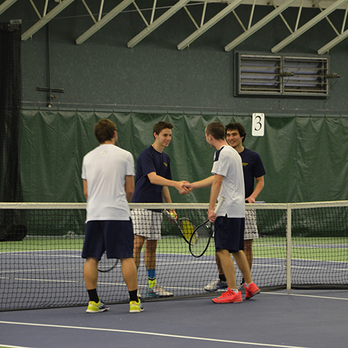 Players from both schools shake hands to start a match