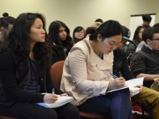 Attendees listening and taking notes.