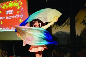 A student performing a traditional fan dance.