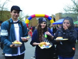 Students eating free food at the barbecue.