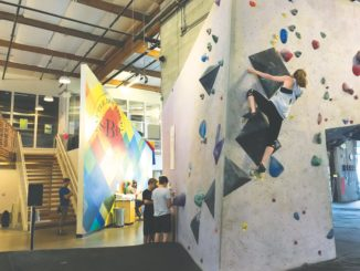 Climber scales a wall.