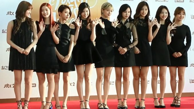 a group of women in formal dresses posing in front of a backdrop